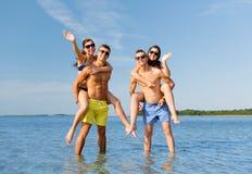 Amigos sonrientes en gafas de sol en la playa del verano Fotos de archivo