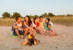 Amigos sonrientes en gafas de sol en la playa del verano Imagen de archivo