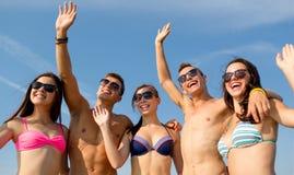 Amigos sonrientes en gafas de sol en la playa del verano Fotografía de archivo libre de regalías