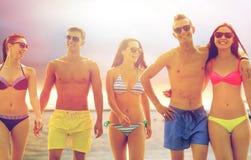 Amigos sonrientes en gafas de sol en la playa del verano Imagenes de archivo