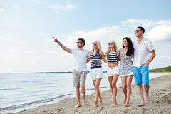 Amigos sonrientes en gafas de sol que caminan en la playa Imágenes de archivo libres de regalías