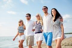 Amigos sonrientes en gafas de sol que caminan en la playa Imagen de archivo
