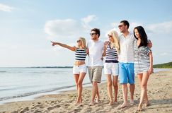 Amigos sonrientes en gafas de sol que caminan en la playa Imagenes de archivo