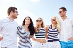 Amigos sonrientes en gafas de sol que hablan en la playa Fotografía de archivo libre de regalías