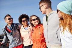 Amigos sonrientes en gafas de sol que ríen en la calle Fotos de archivo libres de regalías