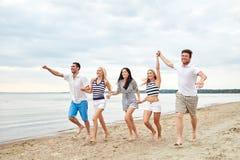 Amigos sonrientes en las gafas de sol que corren en la playa Foto de archivo