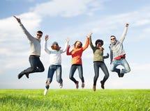 Amigos sonrientes en las gafas de sol que saltan arriba Fotos de archivo libres de regalías