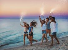 Amigos sonrientes felices que corren en la playa con las velas chispeantes Fotos de archivo