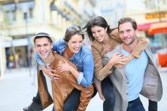 Amigos sonrientes felices que se divierten en las calles Imagenes de archivo