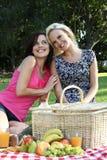 Amigos sonrientes magníficos de las mujeres en la comida campestre Foto de archivo