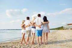 Amigos sonrientes que abrazan y que caminan en la playa Fotografía de archivo