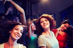 Amigos sonrientes que bailan en club Foto de archivo