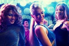 Amigos sonrientes que bailan en club Fotografía de archivo libre de regalías