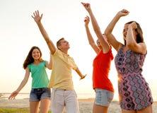 Amigos sonrientes que bailan en la playa del verano Foto de archivo libre de regalías