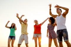 Amigos sonrientes que bailan en la playa del verano Imagen de archivo