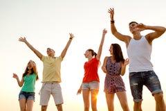 Amigos sonrientes que bailan en la playa del verano Imagen de archivo libre de regalías