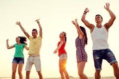 Amigos sonrientes que bailan en la playa del verano Foto de archivo