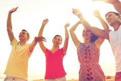 Amigos sonrientes que bailan en la playa del verano Imagenes de archivo
