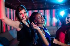 Amigos sonrientes que bailan en sala de baile Fotografía de archivo