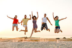 Amigos sonrientes que bailan y que saltan en la playa Foto de archivo libre de regalías