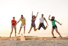 Amigos sonrientes que bailan y que saltan en la playa Imagen de archivo