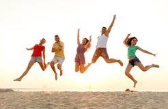 Amigos sonrientes que bailan y que saltan en la playa Fotografía de archivo