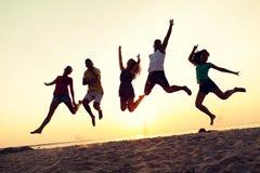 Amigos sonrientes que bailan y que saltan en la playa Imágenes de archivo libres de regalías