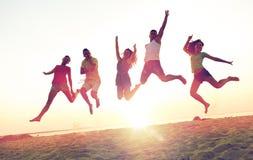 Amigos sonrientes que bailan y que saltan en la playa Imagen de archivo libre de regalías