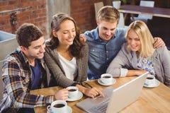 Amigos sonrientes que beben el café y usar el ordenador portátil Fotografía de archivo libre de regalías