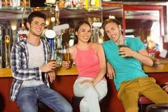 Amigos sonrientes que beben la cerveza junta Imagen de archivo libre de regalías