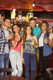 Amigos sonrientes que beben la cerveza y la bebida mezclada Imágenes de archivo libres de regalías
