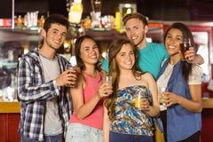 Amigos sonrientes que beben la cerveza y la bebida mezclada Foto de archivo libre de regalías