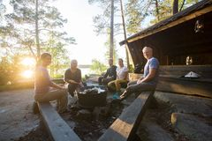 Amigos sonrientes que cocinan la comida en Firepit en el bosque Imágenes de archivo libres de regalías