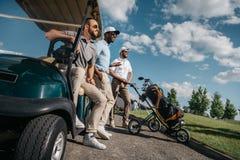 Amigos sonrientes que colocan el carro de golf cercano y que miran lejos Imagen de archivo