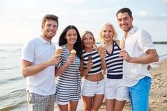 Amigos sonrientes que comen el helado en la playa Foto de archivo libre de regalías