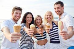 Amigos sonrientes que comen el helado en la playa Imagen de archivo