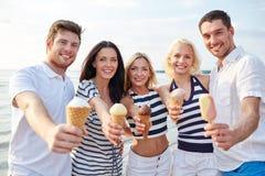 Amigos sonrientes que comen el helado en la playa Fotos de archivo