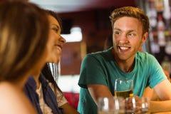 Amigos sonrientes que hablan y que beben la cerveza Fotos de archivo