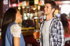 Amigos sonrientes que hablan y que beben la cerveza y la bebida mezclada Fotos de archivo