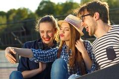Amigos sonrientes que hacen el selfie al aire libre Imagen de archivo libre de regalías