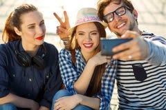 Amigos sonrientes que hacen el selfie al aire libre Imágenes de archivo libres de regalías