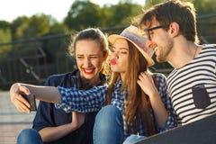 Amigos sonrientes que hacen el selfie al aire libre Foto de archivo libre de regalías