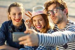 Amigos sonrientes que hacen el selfie al aire libre Fotos de archivo libres de regalías