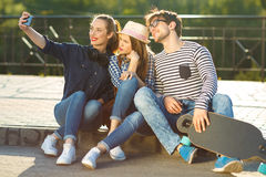 Amigos sonrientes que hacen el selfie al aire libre Foto de archivo