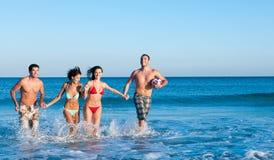Amigos sonrientes que juegan en la playa foto de archivo libre de regalías