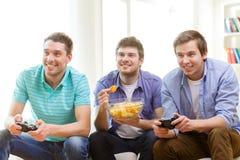 Amigos sonrientes que juegan a los videojuegos en casa Imágenes de archivo libres de regalías