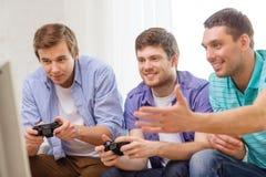 Amigos sonrientes que juegan a los videojuegos en casa Imagen de archivo