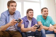 Amigos sonrientes que juegan a los videojuegos en casa Foto de archivo
