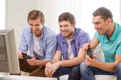 Amigos sonrientes que juegan a los videojuegos en casa Fotos de archivo