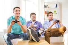 Amigos sonrientes que juegan a los videojuegos en casa Imagen de archivo libre de regalías